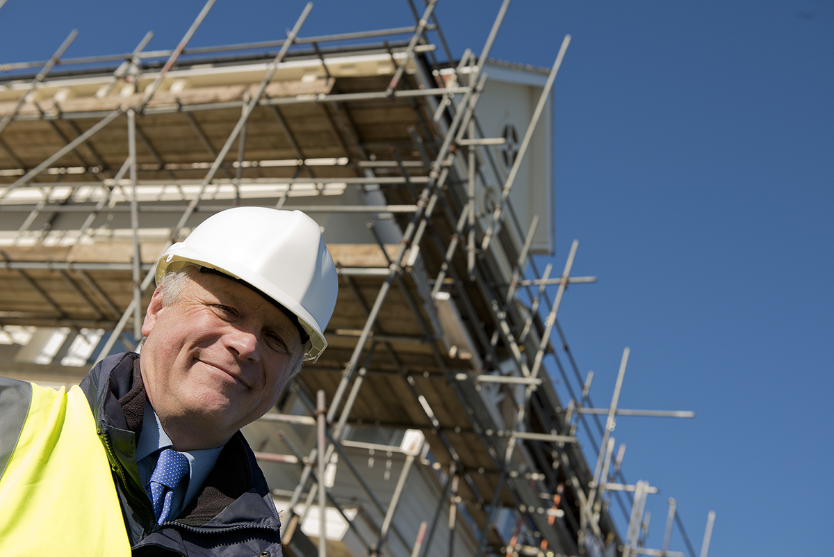 Low angle/tilted view of a smiling building inspector/construction worker, standing beneath a structure, which is under construction with a clear blue sky in the background.